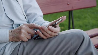 Close Old Senior's Hand Scrolling on Smartphone at Park's Bench