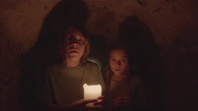 Medium Shot of Scared Kids Standing in Dark with Candle