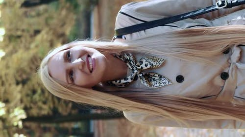 Beautiful Young Blonde Girl Walking in the Park in Autumn and Smiling