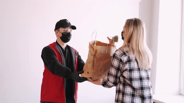 Deliveryman Is Diving a Craft Paper Bag To a Woman in Mask