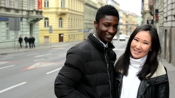 Thumbnail for Happy Couple Smile To Camera - Black Man and Asian Woman - Urban Street with Cars - City