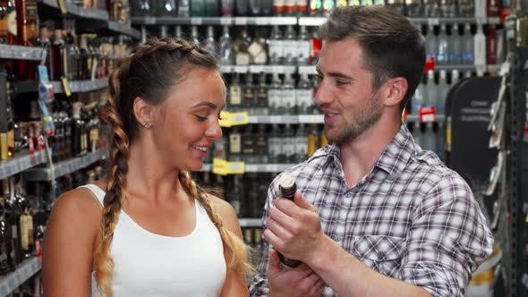 Cover Image for Young Couple Choosing Wine To Buy at the Supermarket