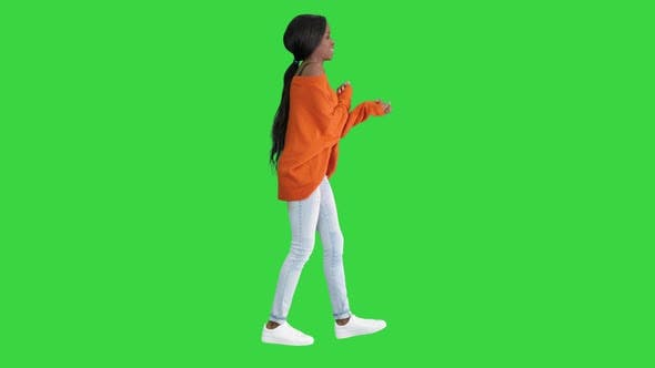 Young Casual African Woman Dancing on a Green Screen, Chroma Key.
