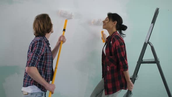 Thumbnail for Excited Carefree Couple Having Fun Painting Wall
