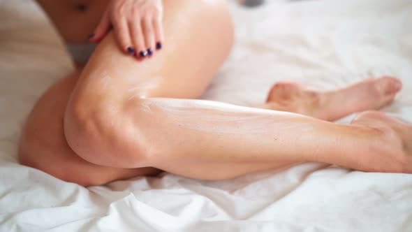 Woman with Perfect Body Applying Moisturizer Cream Body Lotion on Her Slim Legs