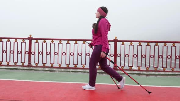 Thumbnail for Nordic walking. Young chubby Caucasian woman hiking with the Nordic poles. Side Follow Shot.