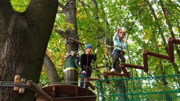 Rope park. A little girl with an instructor overcomes obstacles suspended steps.