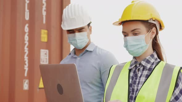 engineer worker walk and talk about work on laptop in construction site