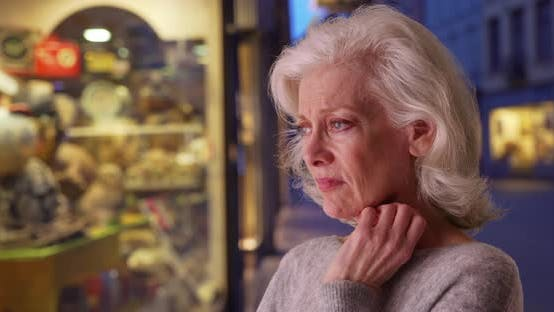 Thumbnail for Stressed senior woman looking in store window shopping for gift at night