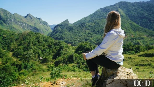 Rear View of a Young Woman Sitting on a Mountain Top