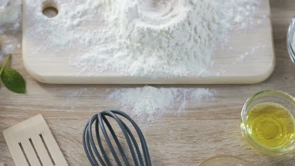 Thumbnail for Housewife breaking egg into flour on kitchen board, making dough by pie recipe