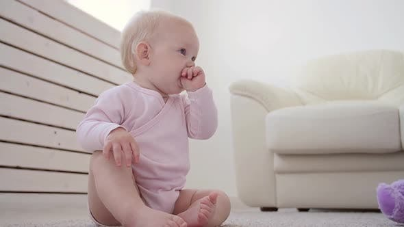 Childhood, Babyhood and Family Concept - Happy Little Baby Boy or Girl Sitting on Floor at Home