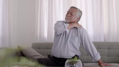 Asian Elderly have back pain. On the sofa in the living room.
