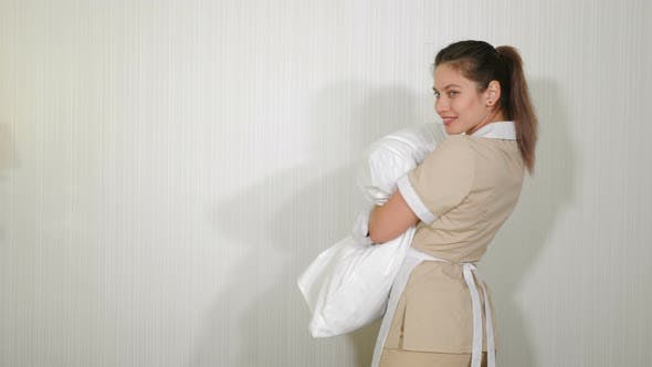 Pretty Maid Hugging Pillow. Cleaning in Cosy Hotel Apartment. Preparation of Hotel Room or Private