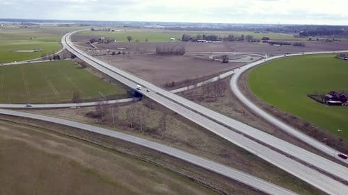 Top down aerial view of highway intersection with moving traffic cars.