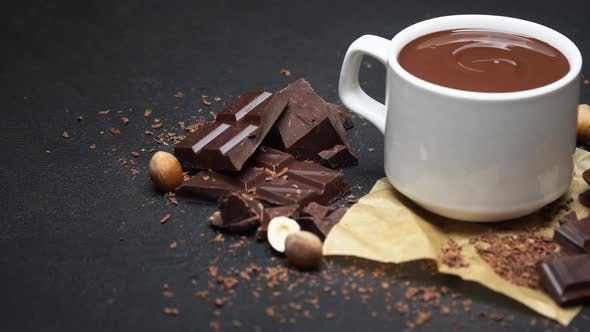 Cover Image for Cup of Hot Chocolate and Pieces of Chocolate on Dark Concrete Background