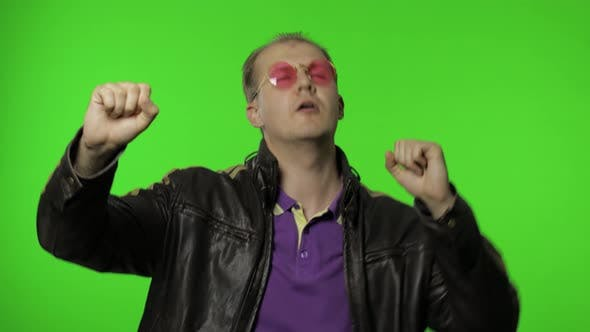 Thumbnail for Playful Rocker Man in Pink Sunglasses Moving in Dance, Smiling, Making Dab Poses, Gesture of Success