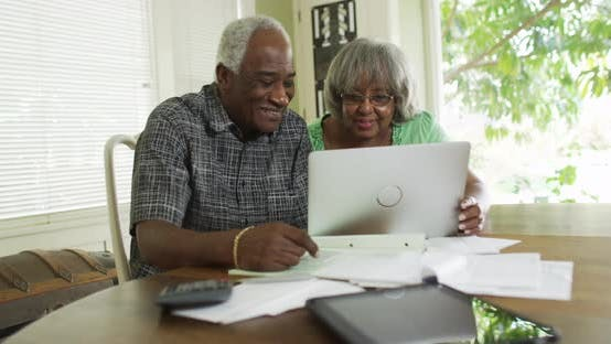 Happy senior African couple paying off bills on laptop