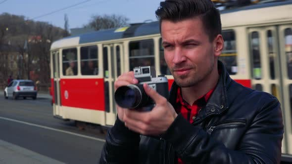 Thumbnail for A Young Handsome Man Takes Photos with a Camera - Closeup - a Busy Road in the Blurry Background