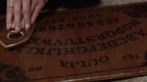 Woman'S Hands Moving Over Ouija Board