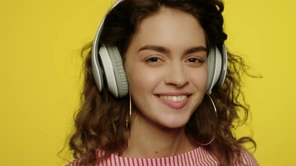 Thumbnail for Young Woman Listen Music in Headphones. Happy Girl in Headphone on Yellow