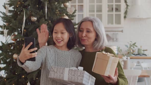 Thumbnail for Happy Asian Grandma and Little Girl Web Calling on Phone on Christmas