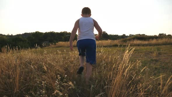 Thumbnail for Following for Young Boy Running on Green Grass at the Field. Little Child Jogging at the Lawn