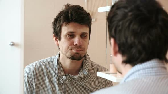 Thumbnail for Tired Man Who Has Just Woken Up Looks at His Reflection in the Mirror and Sees His Scruffy