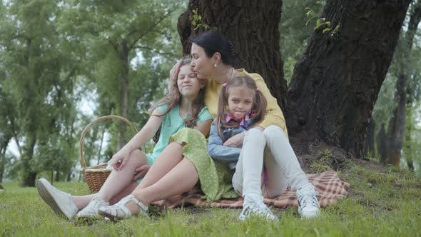 Cover Image for Portrait Senior Woman Kissing and Hugging Cute Granddaughters Sitting on the Grass Under the Tree