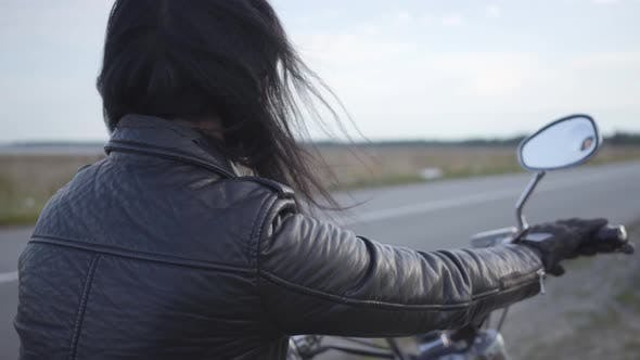 Thumbnail for Back View of Unrecognizable Girl in Old Leather Jacket Sitting on the Motorcycle Looking Away. Hobby