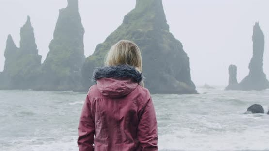 Woman Travel is Walking Along Reynisfjara Beach or Black Sand Beaches in Rain Weather Conditions