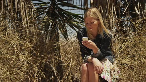 Thumbnail for Happy woman texting on smartphone outdoors