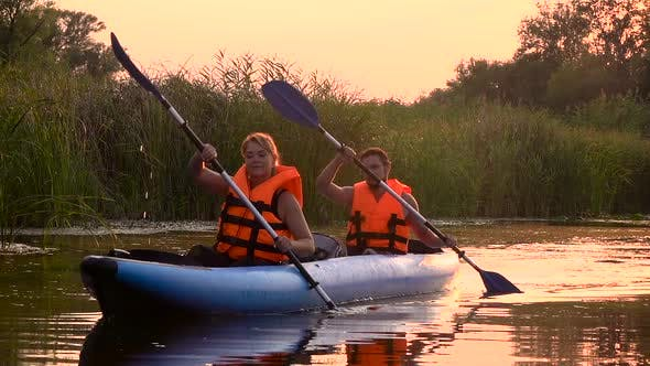 Thumbnail for Two People in Rowing Oars Sitting in a Kayak on the Lake in the Sunset. Slow Motion