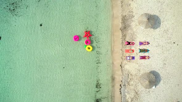 Thumbnail for Aerial view of people lying in yoga pose on on the with inflatables on beach.
