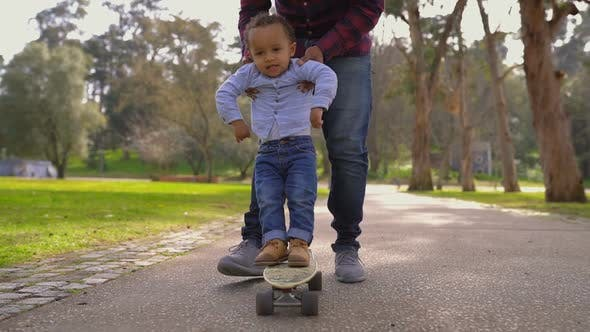 Cover Image for Little Boy Standing on Skateboard, Rolling with Help of Father