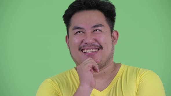 Thumbnail for Face of Happy Young Overweight Asian Man Thinking and Looking Up