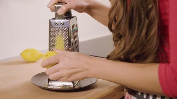 Thumbnail for A Woman Grates a Lemon in a Kitchen - Closeup