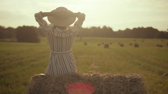Young woman in hat enjoys life in the field