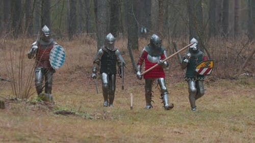 Four Men Knightes Walking in the Row in the Forest in Full Armour