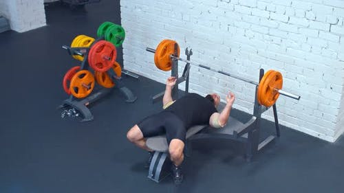 Brutal Man Powerlifter Lays on a Sports Bench, Takes the Barbell. Powerlifter Shakes Chest Muscles