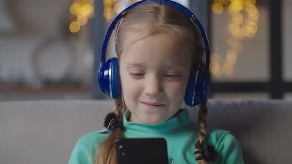 Cover Image for Little Girl in Headphones Enjoying Music on Phone