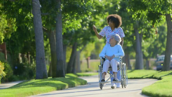 Thumbnail for Nurse walking with elderly woman in wheelchair