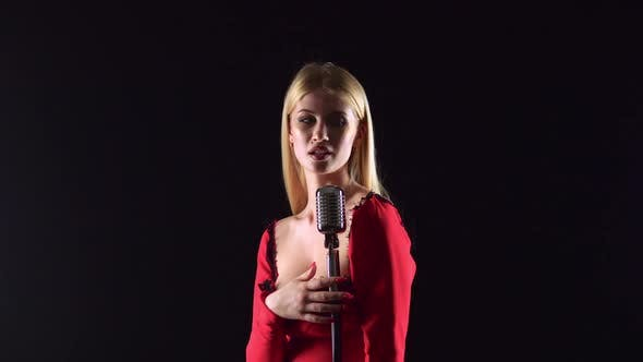 Thumbnail for Girl in a Red Dress Is Singing Into a Retro Microphone. Black Background