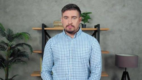 Portrait sad businessman standing in modern office turns head looking camera