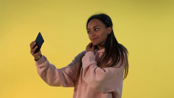 Thumbnail for Cheerful Mixed-race Lady Making Selfie on Smartphone on Yellow Background