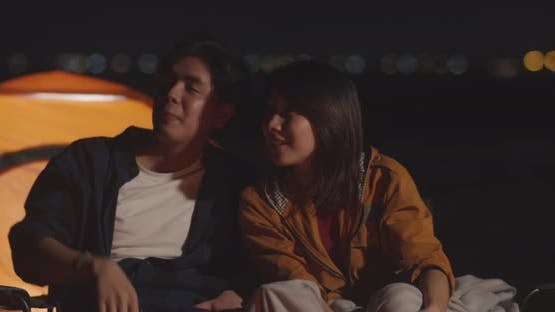 Young asia couple backpackers looking sky in camp at night near campfire on beach.