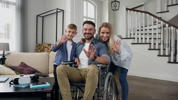 Thumbnail for Glückliche Familie, wo junge bärtige Papa sitzt im Rollstuhl Blick auf die Kamera