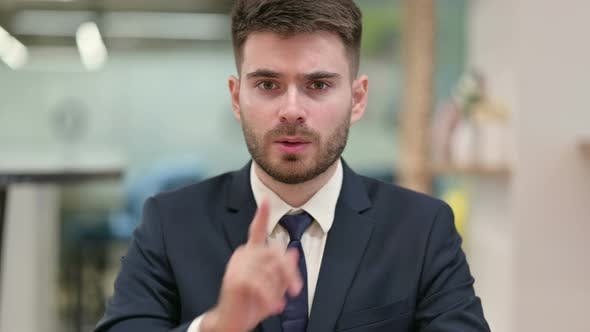Thumbnail for Young Businessman Putting Finger on Lips
