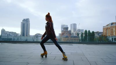 Sporty Ginger Woman Performing Elements of Rollerblading on Urban Background
