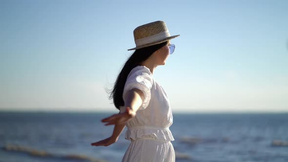 Thumbnail for Woman Traveller with Arms Raised Looking at Sea